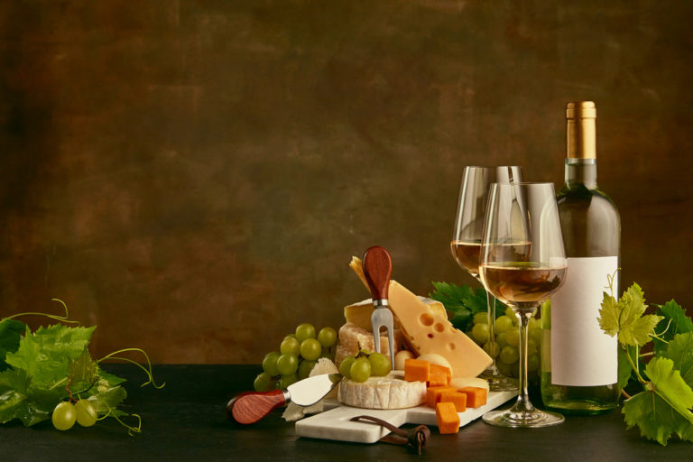 Front view of tasty cheese plate with the wine bottle on dark studio background